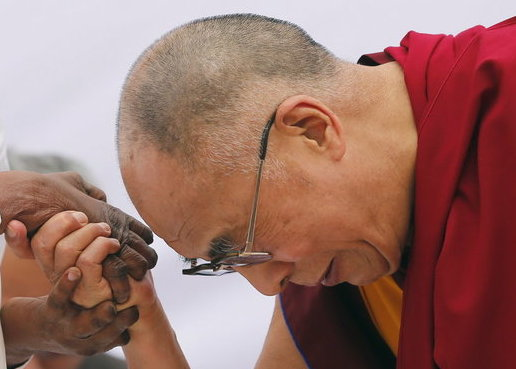 HH Dalai Lama holding the hands of a leper in India, March 2014