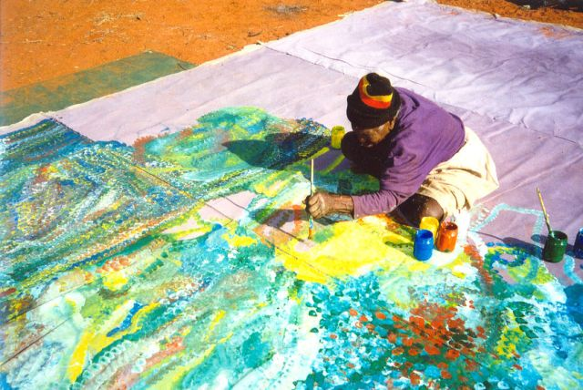 "Emily Kngwarreye working on the painting ""Earth's Creation"""